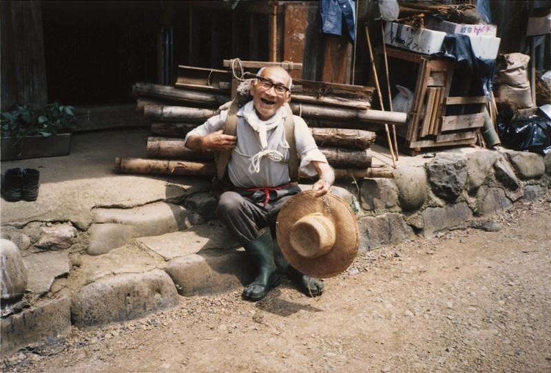 坂本信綱さんの竹負い。八十歳余りでも畑で使っていた垣も薪物にするといって山からオンデ(背負って)帰った。「やれやれ家まで着いたぞ」。1981年
